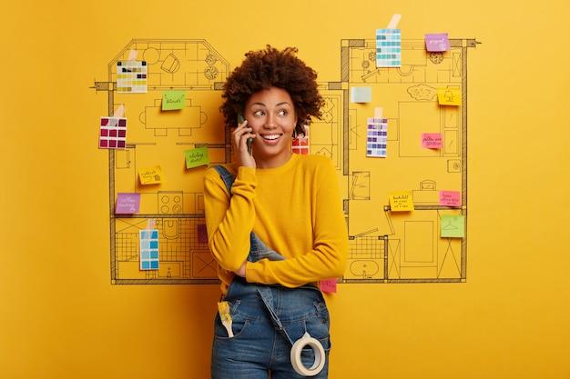 현대 아파트의 리노베이션을 계획하는 행복 한 젊은 여자 디자이너