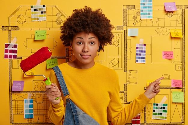 モダンなアパートの改修を計画している幸せな若い女性デザイナー