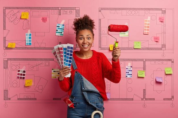 モダンなアパートの改修を計画している幸せな若い女性デザイナー 無料写真