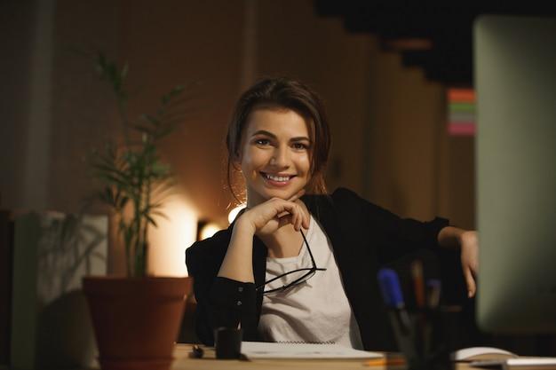 夜のオフィスに座って幸せな若い女性デザイナー