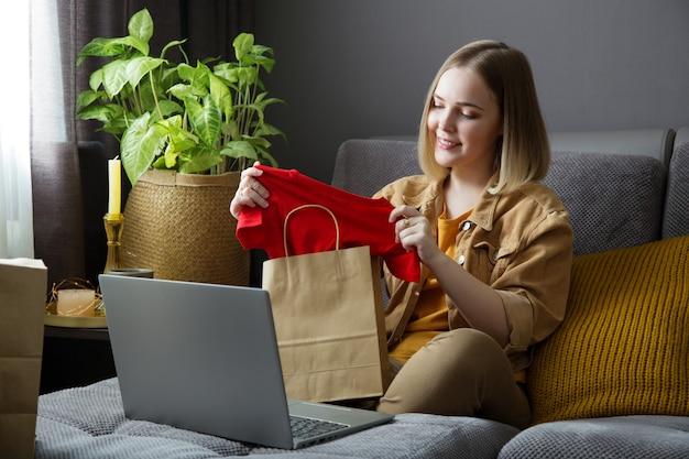 幸せな若い女性は服のオンライン注文を開梱します。オンラインショッピング、注文配送。 10代の少女は、ラップトップでの購入を検討してソファでリラックスします。