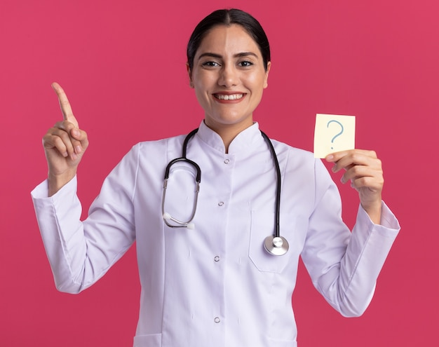 Happy young woman doctor in medical coat with stethoscope holding reminder paper with question mark pointing with index finger up smiling cheerfully standing over pink wall