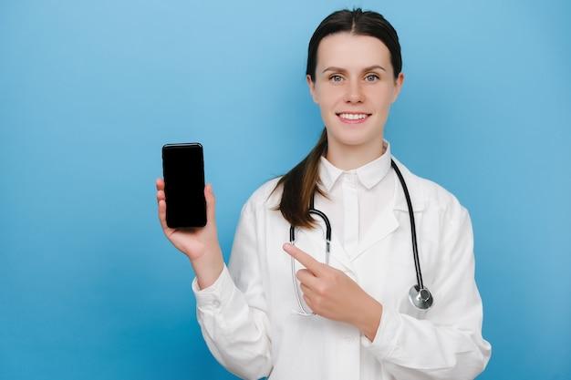幸せな若い女性医師がモバイル画面で指を指して、青い背景で隔離のダウンロード検査、相談アプリケーションをお勧めします。 covid-19、医療従事者とオンライン医療の概念