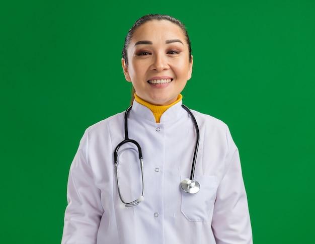 Felice giovane dottoressa in camice bianco con stetoscopio intorno al collo sorridente fiducioso in piedi sul muro verde