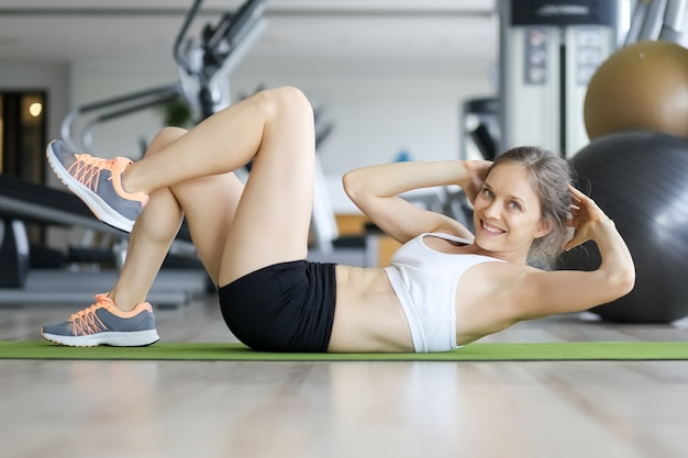 Happy young woman doing crunches on mat in gym