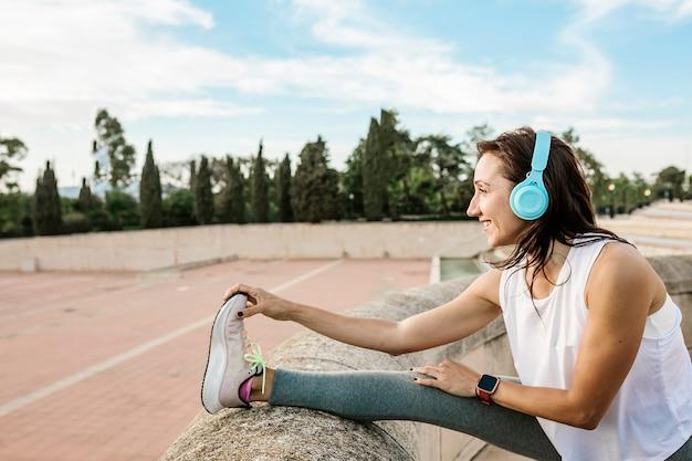 屋外で音楽を聴きながら走る前にストレッチ運動脚をやっている幸せな若い女性