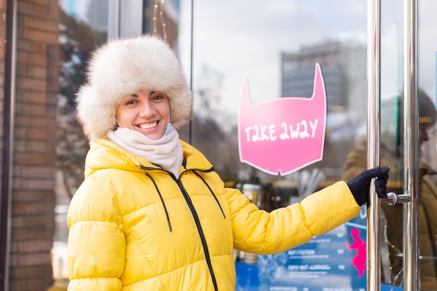 Felice giovane donna alla porta del ristorante in una fredda giornata invernale, scritte, cibo da asporto.