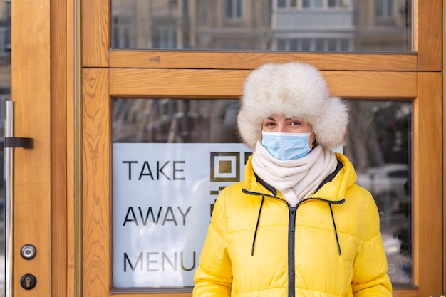 Happy young woman at the door of the restaurant on a cold winter day, lettering, takeaway food.