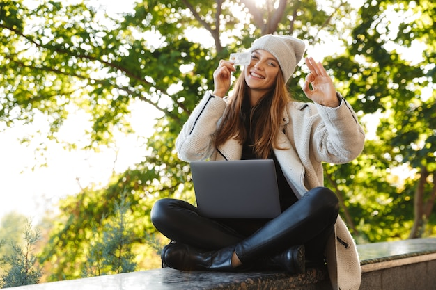 Happy young woman dressed in autumn coat and hat sitting outdoors, using laptop computer, showing plastic credit card