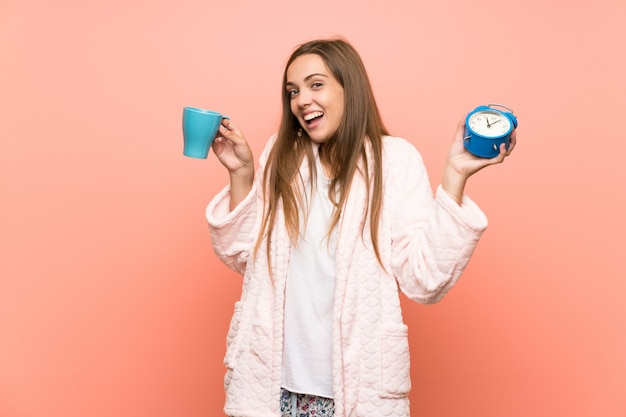 Happy young woman in dressing gown over pink wall holding a cup of coffee