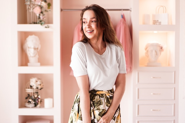Happy young woman dressing up. dressing room in pink colors. the concept of fashion and happiness