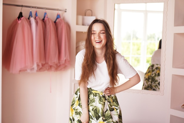 Happy young woman dressing up. dressing room in pink colors