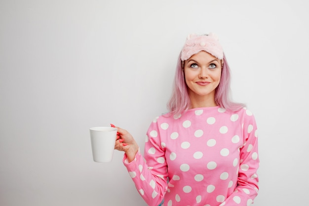 Счастливая молодая женщина пить утренний кофе. красивая девушка в розовой пижаме и маске сна