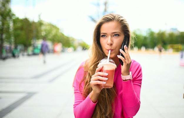 電話で話している間屋外でコーヒーを飲む幸せな若い女性