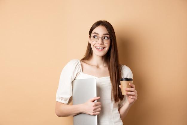행복 한 젊은 여자 커피를 마시고 노트북을 들고, 공부, 베이지 색 배경에 서 밝은 미소로 옆으로 찾고.