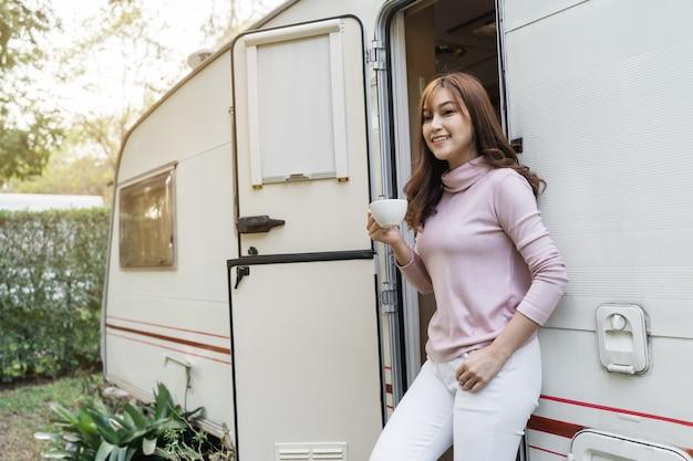 Happy young woman drinking coffee at door of a camper rv van motorhome