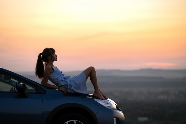Happy young woman driver in blue dress enjoying warm summer evening laying on her car hood. travelling and vacation concept.