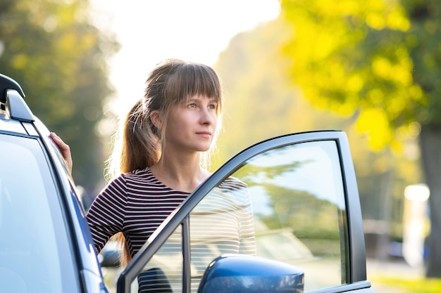 도시 거리에서 그녀의 차 옆에 서서 따뜻한 여름날을 즐기는 행복한 젊은 여성 운전사.