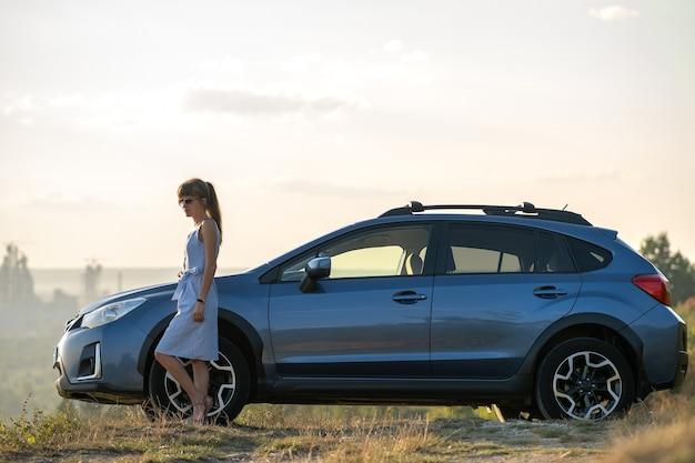 彼女の車の横に立って暖かい夏の夜を楽しんで青いドレスを着た幸せな若い女性ドライバー。