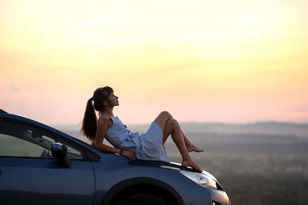 Счастливый водитель молодой женщины в голубом платье кладя на капот автомобиля, наслаждаясь теплым летним днем.