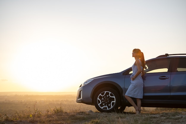 暖かい夏の日を楽しんでいる彼女の車にもたれて青いドレスの幸せな若い女性ドライバー。旅行や休暇の概念。