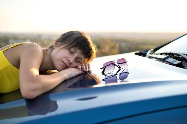 Счастливый водитель молодой женщины в желтом платье, наслаждаясь теплым летним вечером, опираясь на ее автомобиль.