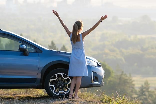 Счастливый водитель молодой женщины с протянутыми вверх руками, наслаждаясь теплым летним вечером, стоя рядом с ее автомобилем. концепция путешествий и отдыха.