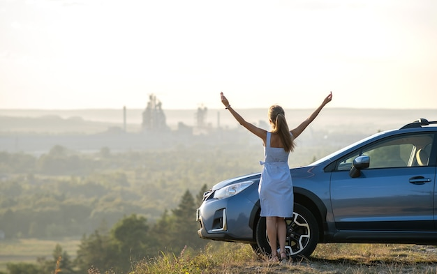 Happy young woman driver with outstretched up hands enjoying warm summer evening standing beside her car. travelling and vacation concept.