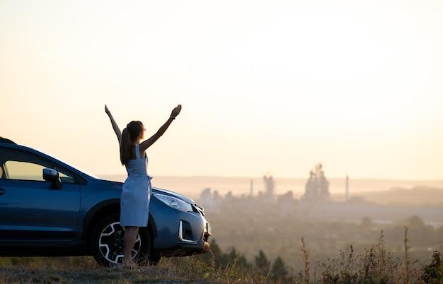 Счастливая молодая женщина-водитель с протянутыми вверх руками, наслаждаясь теплым летним вечером