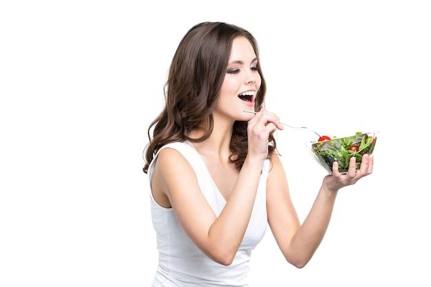 Счастливая молодая женщина ест свежий изолированный салат. здоровый образ жизни.