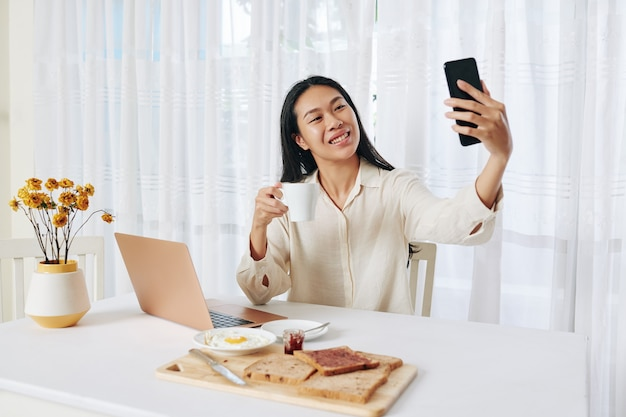 Happy young woman eating breakfast and making business phone call at her desk in living room