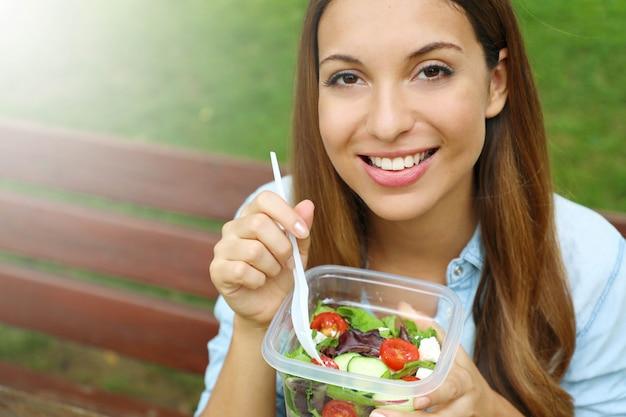 Счастливая молодая женщина ест здоровый салат в парке. скопируйте пространство.