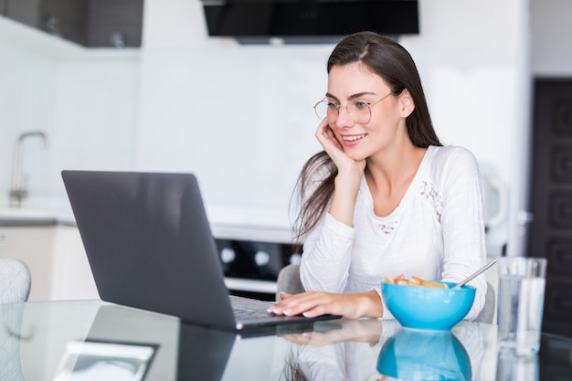 Happy young woman eating salad from a bowl and drinking orange juice while standing on a kitchen and watching movie on laptop