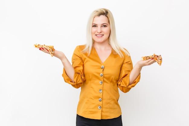 흰색으로 격리된 뜨거운 피자 한 조각을 먹는 행복한 젊은 여성