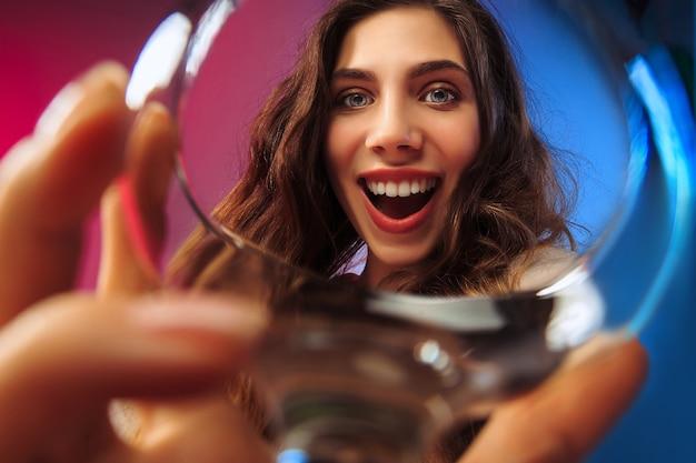 幸せな若い女性。感情的な女性のかわいい顔。ガラスからの眺め