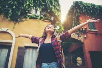 Happy young woman enjoy travel raising her hands in urban. Woman lifestyle concept.
