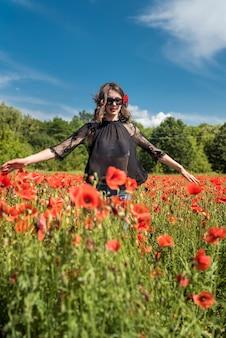 양 귀 비 필드에 자연에서 자유를 즐기는 행복 한 젊은 여자