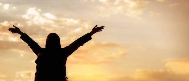 Счастливая молодая женщина, наслаждающаяся свободой с открытыми руками, смотрящая в небо