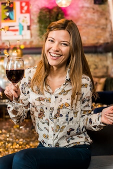Happy young woman enjoying party holding wine glass