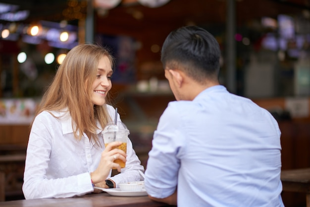 Happy young woman enjoying romantic date with boyfriend at cafe table