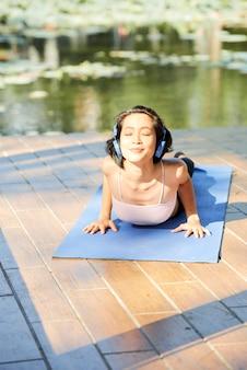 Счастливая молодая женщина наслаждается солнечным утром и слушает музыку в наушниках, делая асаны кобры на открытом воздухе