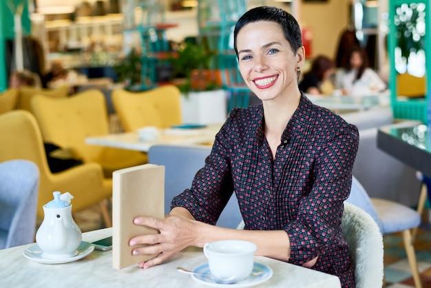 Счастливая молодая женщина, наслаждаясь время в кафе