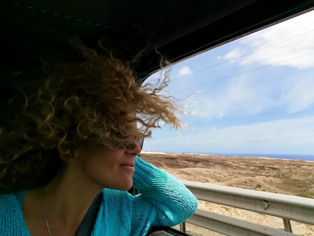 車で旅行しながら旅行を楽しんで幸せな若い女性。窓の外を見ているサングラスの女性。ロードトリップ中に車の窓から自然を賞賛する乱れた髪の女性