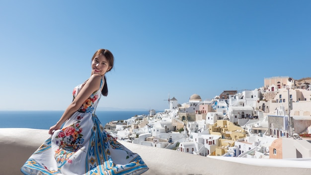 Happy young woman enjoying view oia village in santorini island, greece.