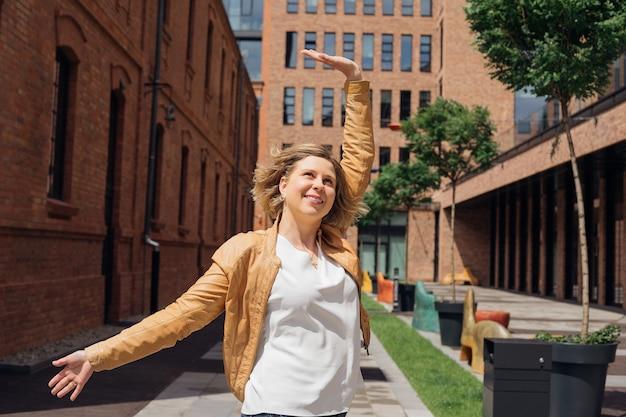 幸せな若い女性は春に街での生活を楽しんでいますが、旅行生活は素晴らしい観光と喜びです...