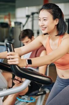 Счастливая молодая женщина, тренирующаяся в тренажерном зале