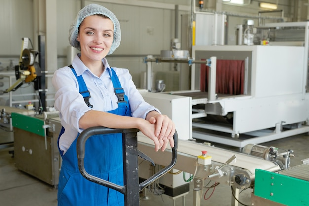 Happy young woman at factory