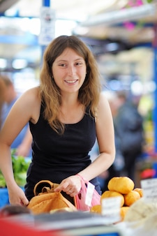 Happy young woman at the farmer market
