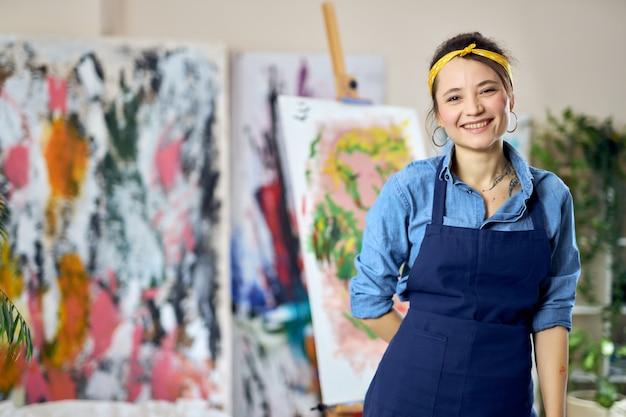 홈 스튜디오 워크샵에서 포즈를 취하는 카메라를 보고 웃고 있는 앞치마를 입은 행복한 젊은 여성 여성 예술가