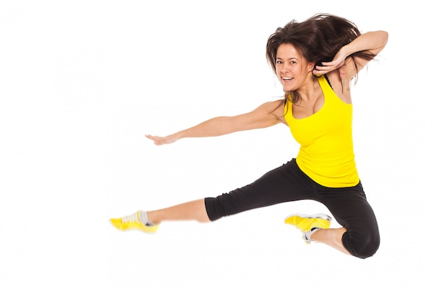 Happy young woman in fitness wear jumps